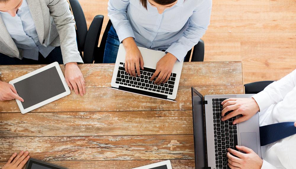 Ryhmä ihmisiä on kokoontunut pöudän ympärille tietokoneiden kanssa