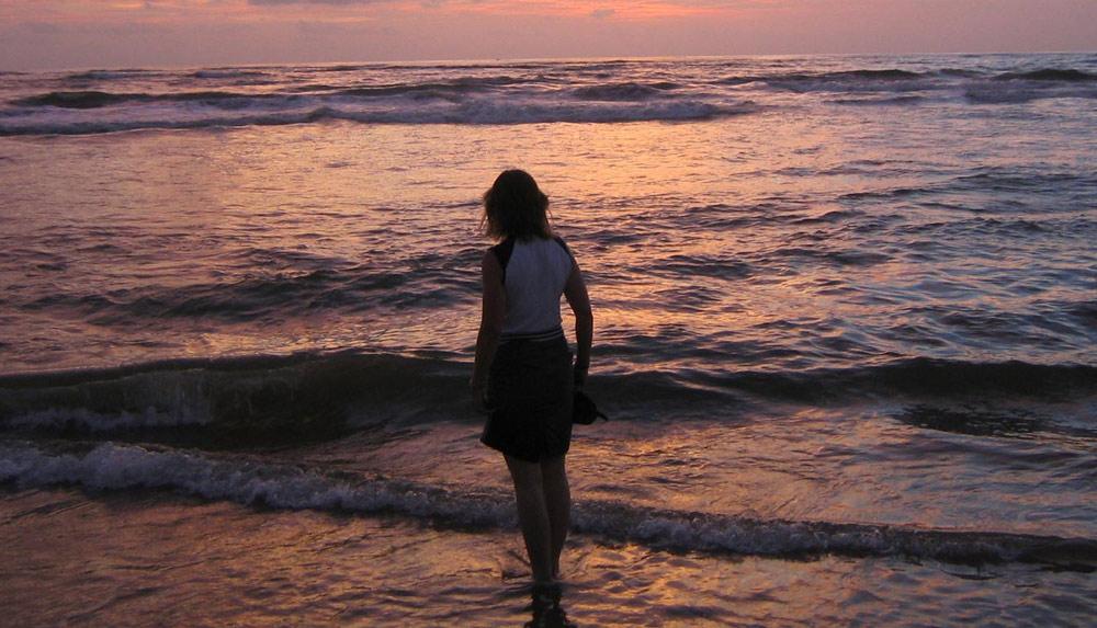 nainen katsoo auringonlaskun värjäämää merta