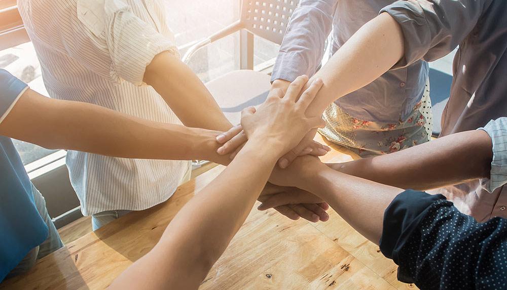 Ryhmä ihmisiä on asettanut kädet yhteen